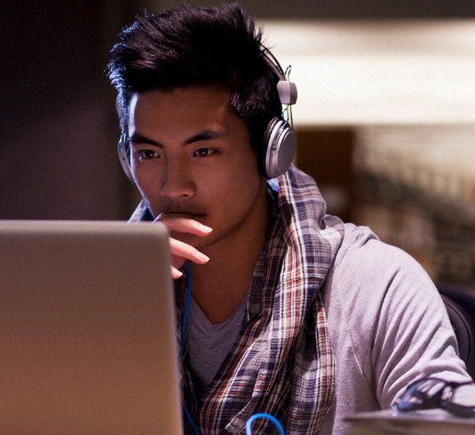 young man looking at a laptop screen