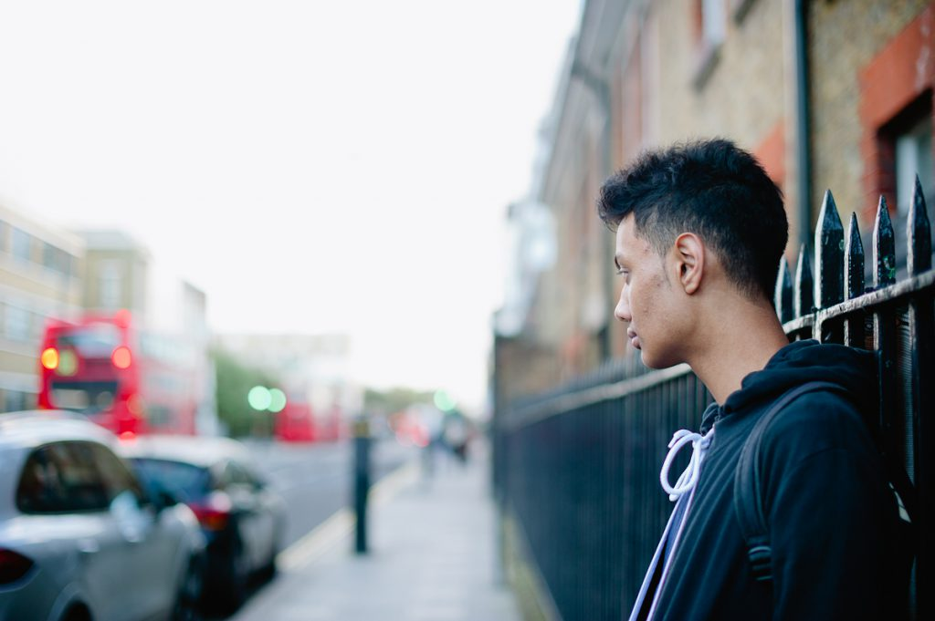 young man standing against street railings