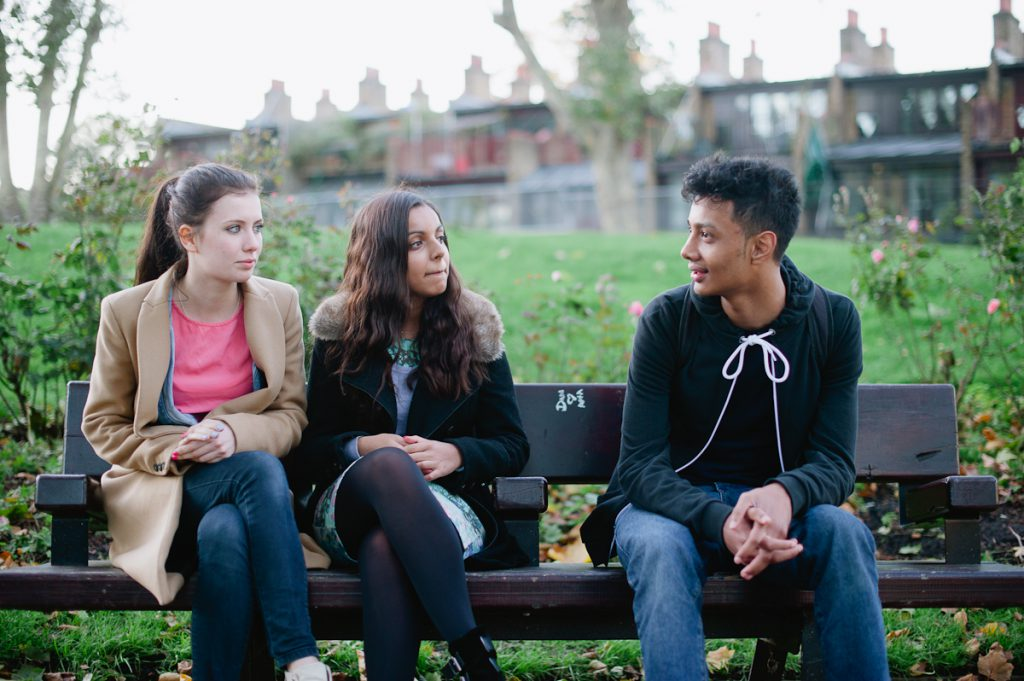 three young people sitting in a park