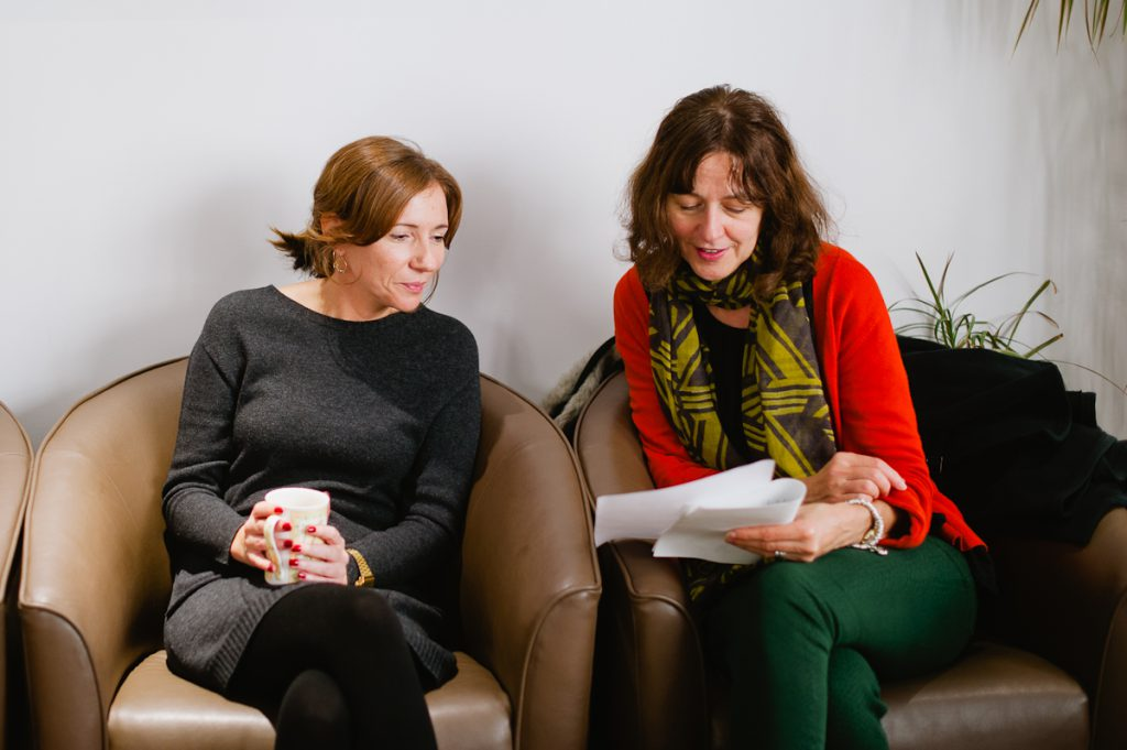 two seated women looking at a printed report