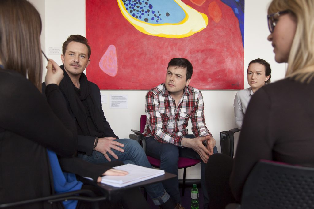group of five people having discussion