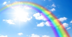 Rainbow against a blue sky with white clouds